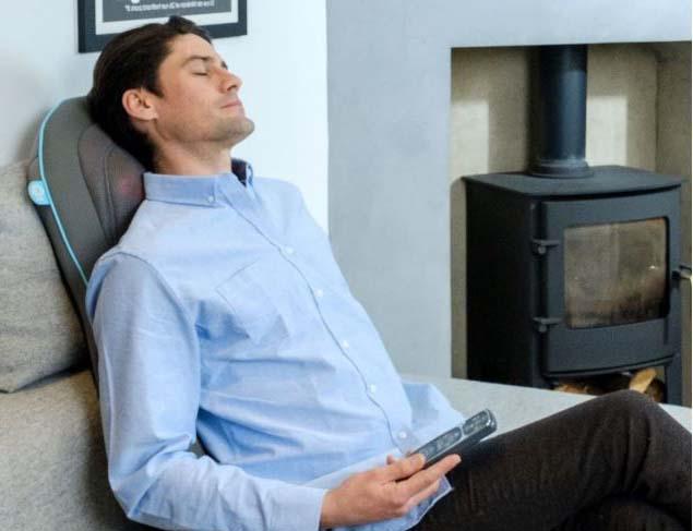 un homme qui est en cours d'utilisation du siège de massage shiatsu homedics avec la technologie gel